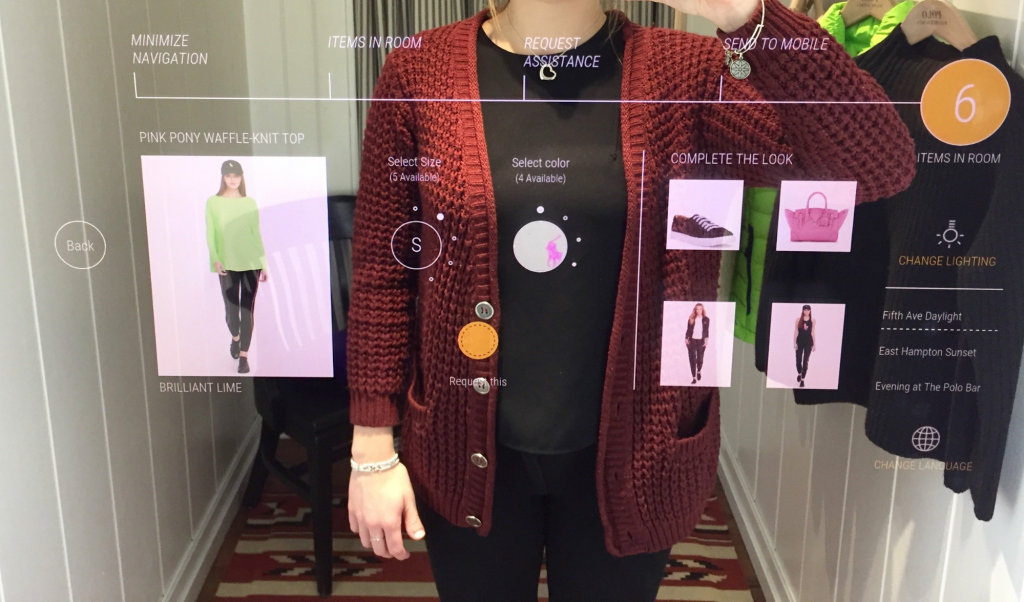 a woman stays at the interactive fitting room and choose clothes