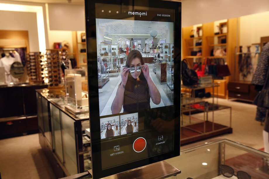 a woman is putting on sunglasses looking at the interactive mirror